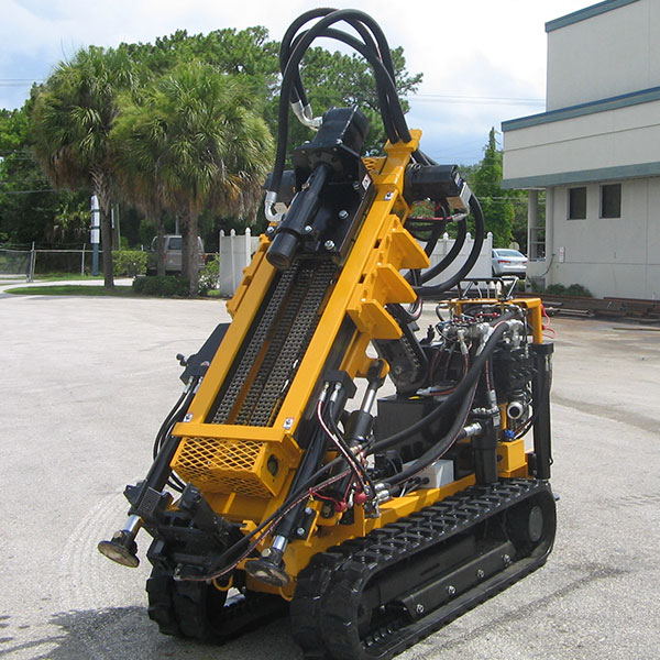 Grout injection compaction grouting drill rig with umbilical hydraulic system.